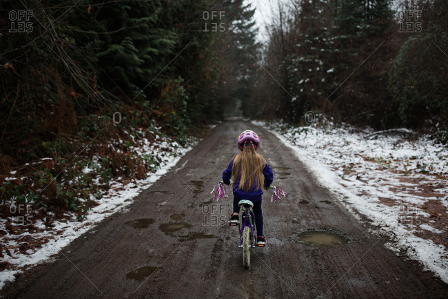 Girl riding bicycle on dirt road through forest in winter