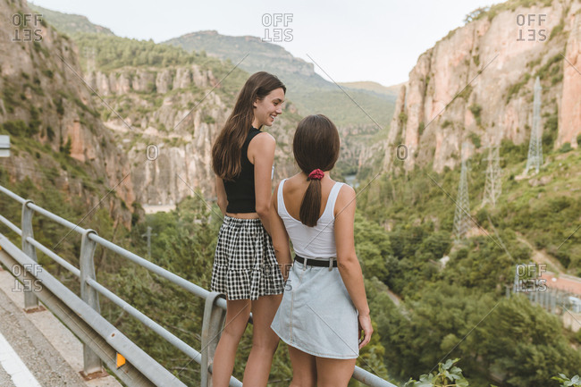 Rear view of couple of girls smiling on a cliff on a sunny afternoon