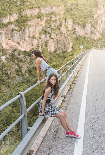 Two girlfriends sitting and observing landscape on a guardrails on the road
