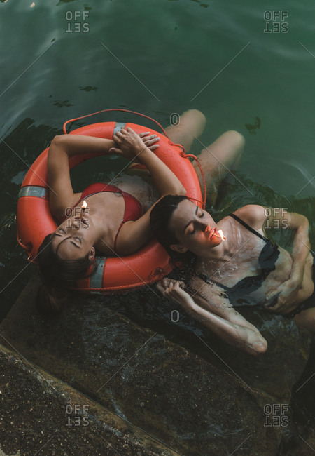 Overhead view of a couple of girls floating with lifebelt with a match lit in their mouths