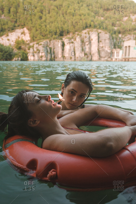 Side view of a couple of girls floating with lifebelt with a match lit in their mouths