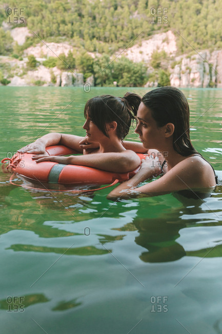 Side view of a couple of girls floating with lifebelt in a lake