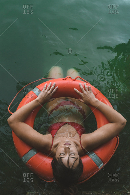 Overhead view of a young girl in orange bikini floating with lifebelt in a lake