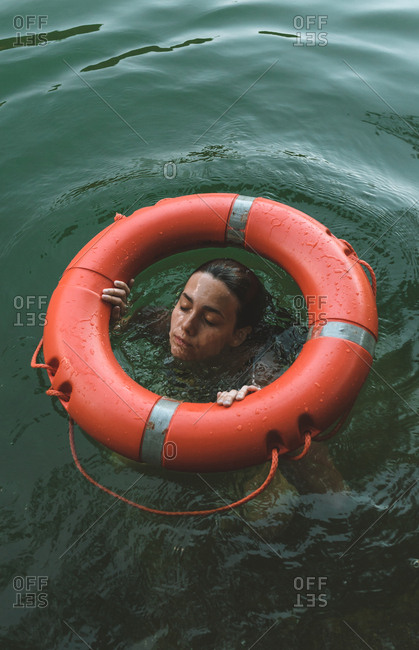 Young brunette woman coming out the water in the middle of a lifesaver
