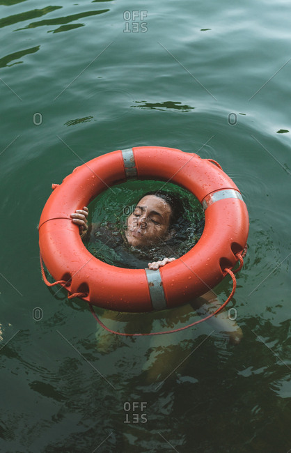 Young brunette woman coming out the water in the middle of a lifebelt