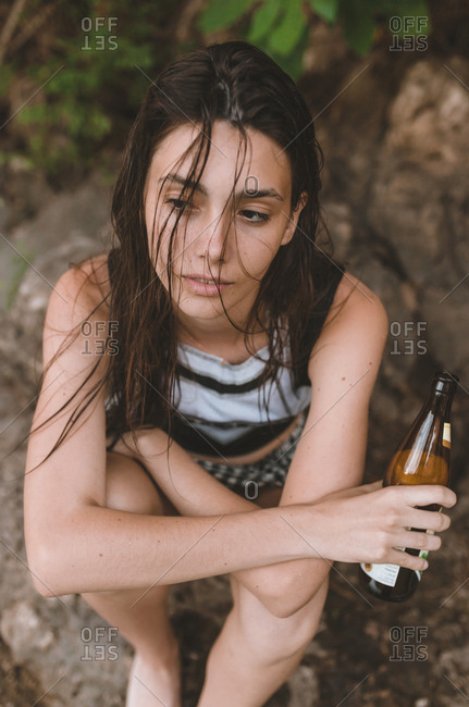 Portrait of a young brunette girl holding a beer