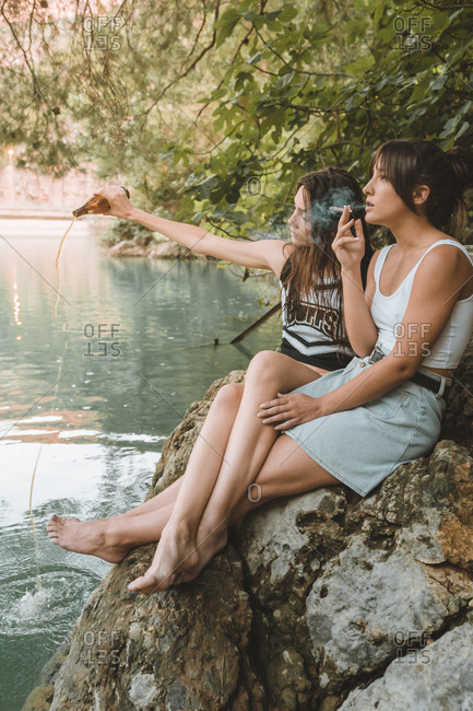 Side view of a couple of girls sitting on a rocks smoking and pouring a beer in the lake
