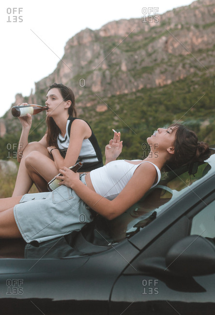 Side view of two girls sitting on the car hood smoking and drinking a beer