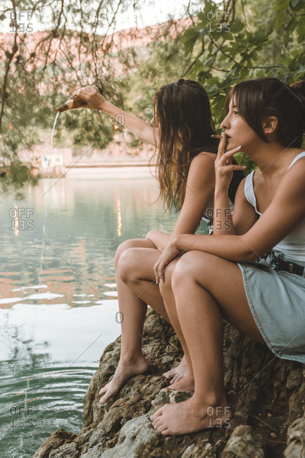 Couple of girls sitting on a rocks smoking and pouring a beer in the lake