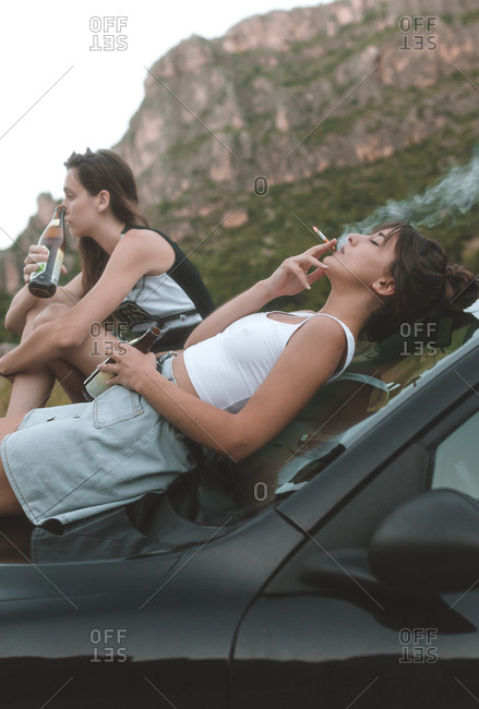 Side view of two girls sitting on the car hood smoking and drinking a beer with mountains in background
