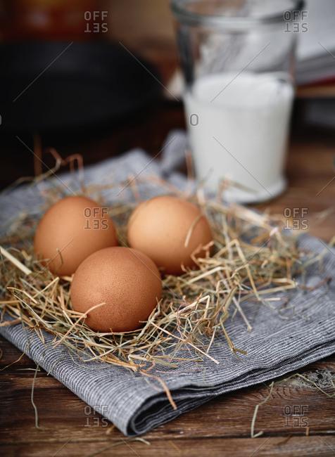 Brown eggs on straw beside glass of milk