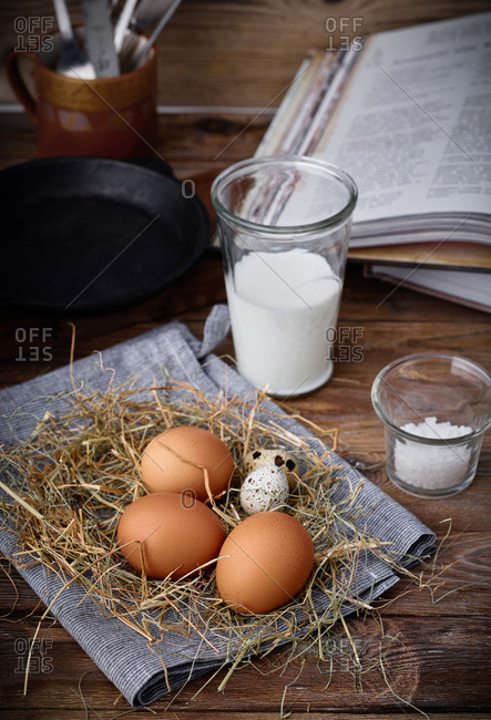 Brown and speckled eggs on straw beside glass of milk