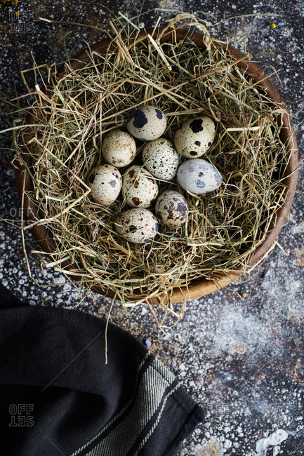 Overhead view of quail eggs on bed of straw in a bowl