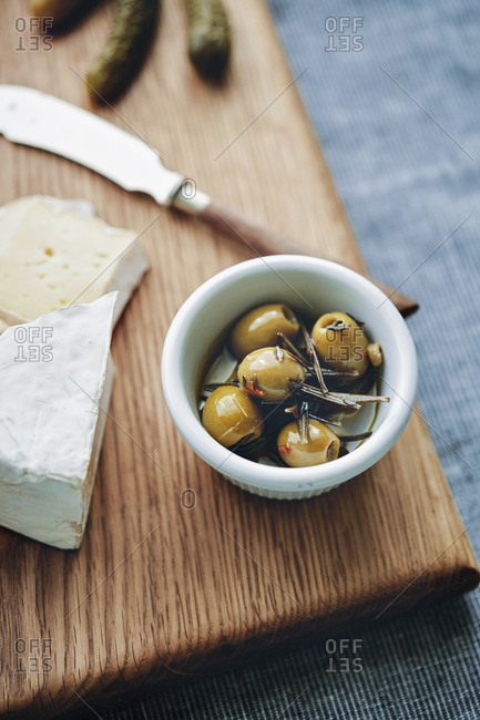 A cheese board with olives