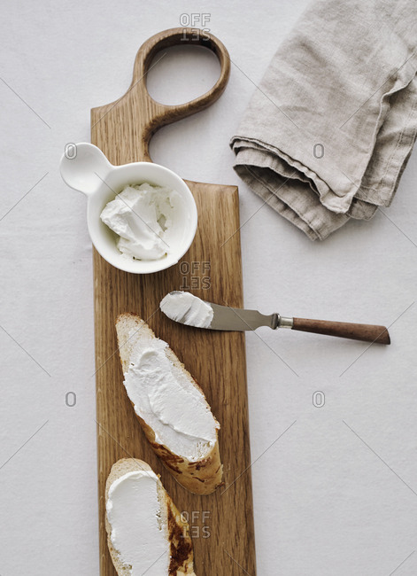 Goat cheese spread onto bread on a wooden board