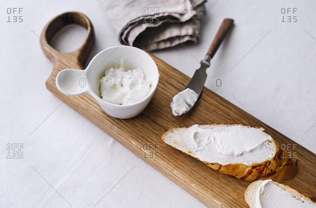 Close up of goat cheese spread onto bread on a wooden board