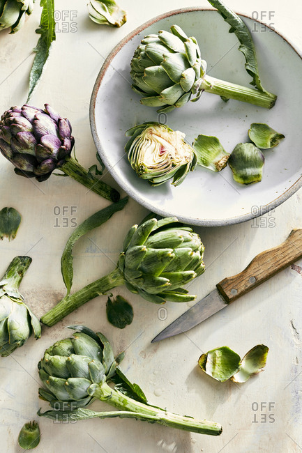 Freshly cut artichokes with bowl and knife