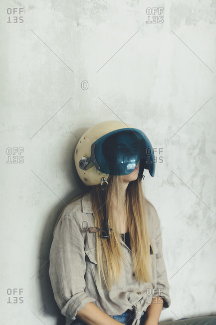 Young woman wearing vintage helmet sitting against wall
