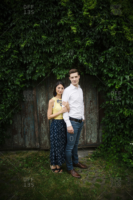 Young engaged couple standing close together in rustic setting