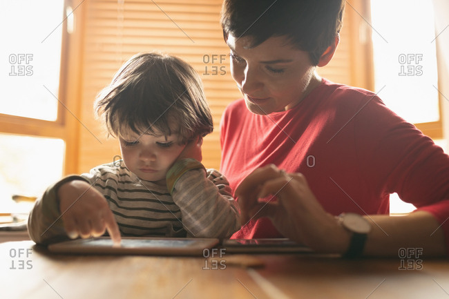 Close-up of mother teaching to son on digital tablet at home