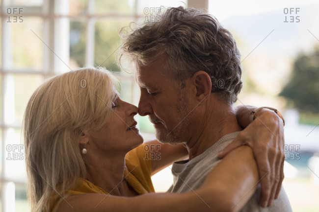 Close-up of romantic senior couple dancing together at home