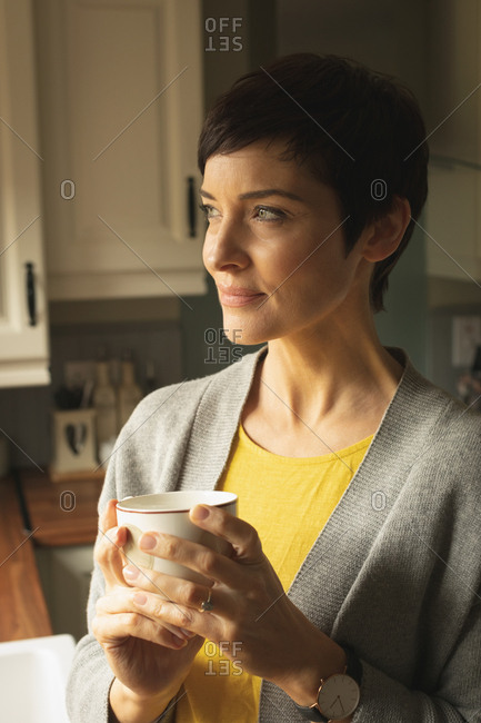 Close-up of thoughtful woman having coffee in the kitchen at home