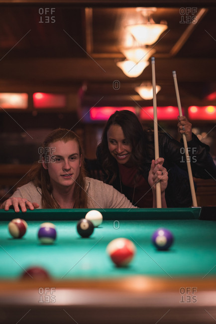 Couple playing snookers in the night club