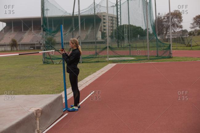 Female athlete adjusting a horizontal bar at sport venue