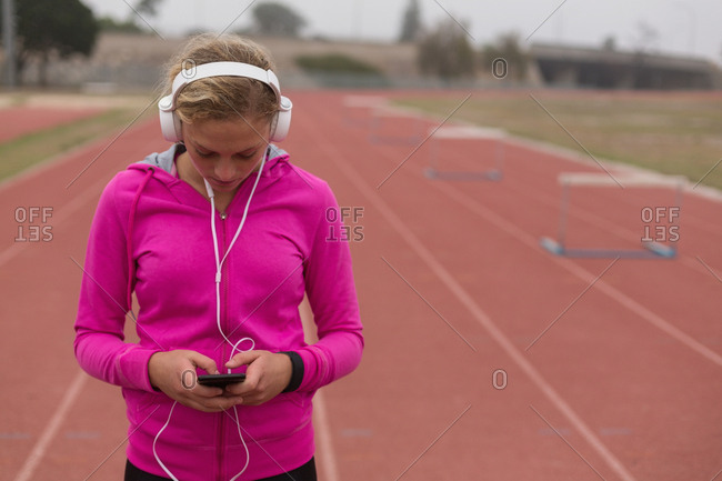 Female athlete listening music on mobile phone at running track