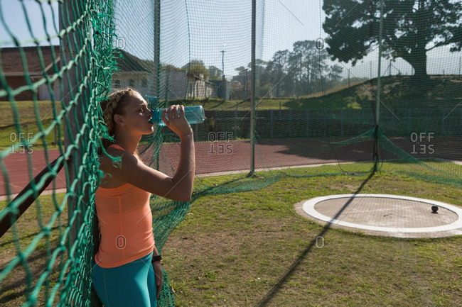 Female athlete drinking water at sports venue