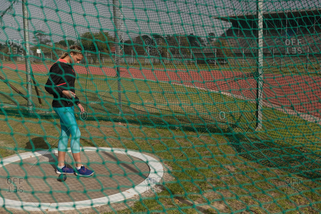 Female athlete practicing shot put at sports venue