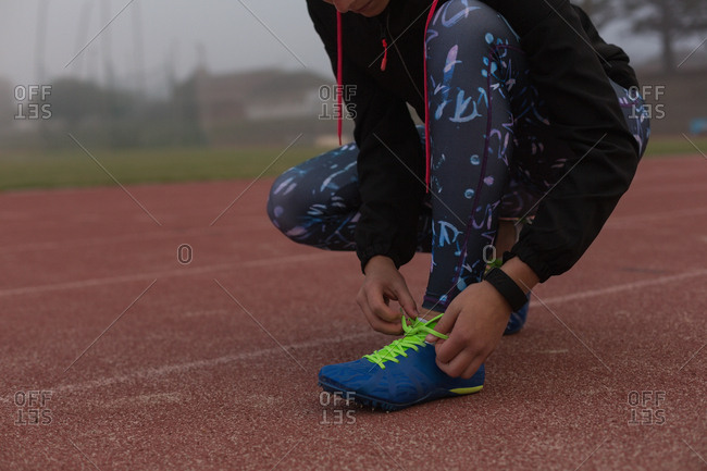 Female athlete tying shoelaces on the running track