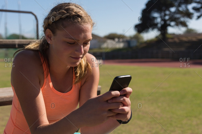 Female athlete using mobile phone at sports venue