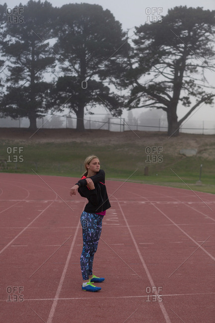 Female athlete warming up on the running track