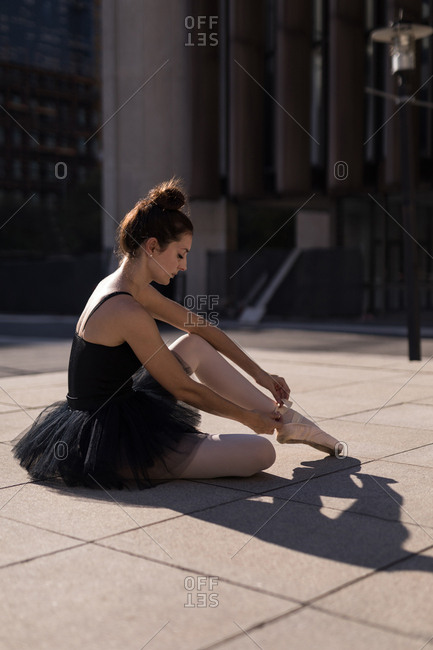 Female ballet dancer tying the ribbon on her ballet shoes in the city