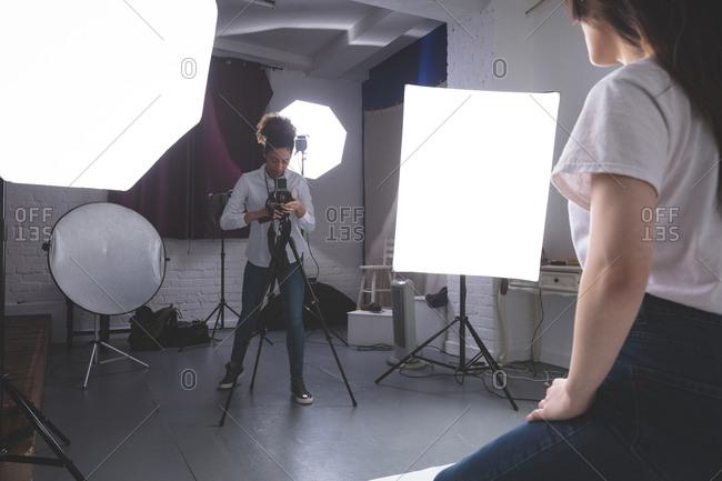 Female photographer clicking photos of model in photo studio