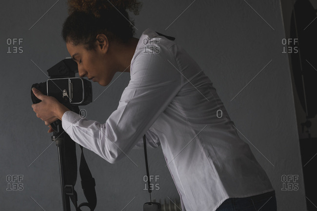 Female photographer clicking photos with digital camera in photo studio