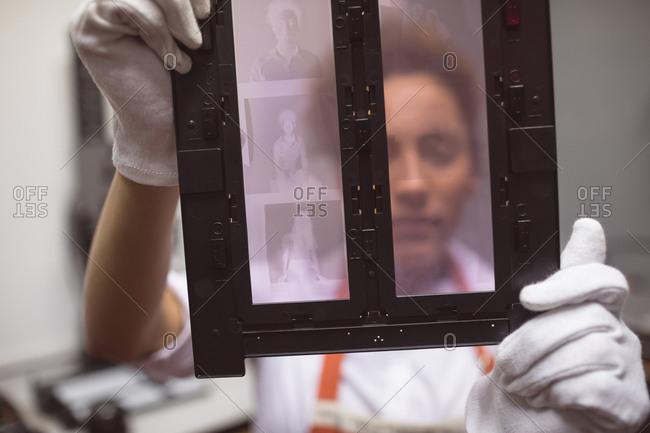 Female photographer holding photo negatives in photo studio