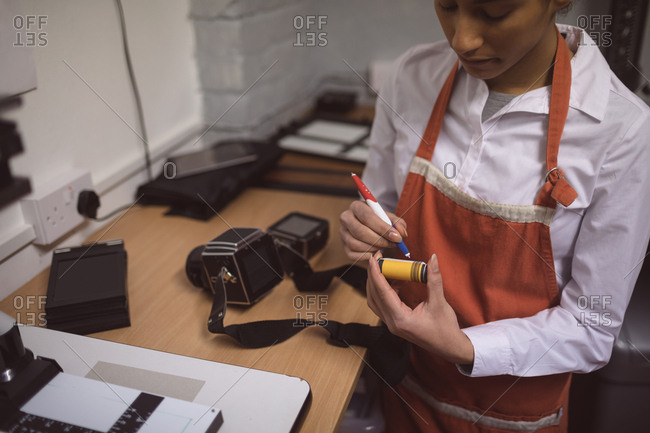 Female photographer marking a photo reel in photo studio