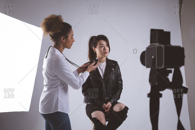 Female photographer recording an interview using voice recorder in photo studio