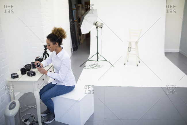 Female photographer removing reel from digital camera in photo studio