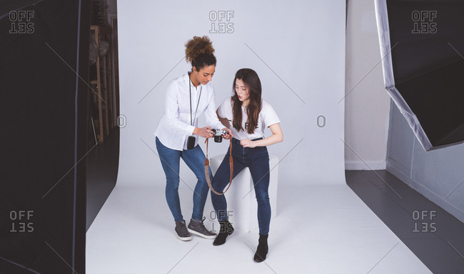 Female photographer showing photos to model in photo studio