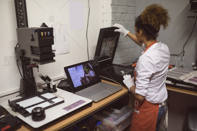 Female photographer using photo scanner in photo studio