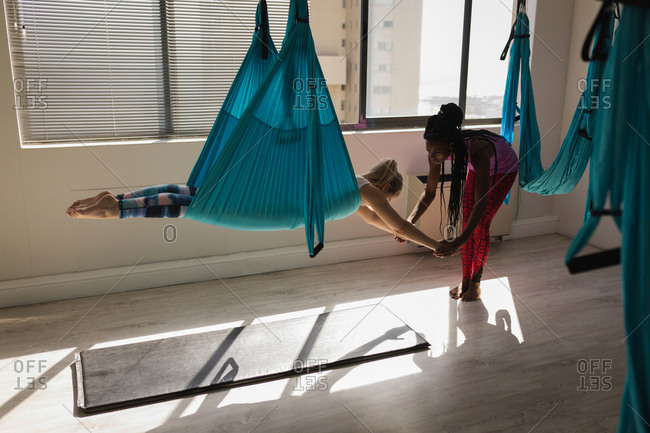 Female trainer assisting woman to exercise on swing sling hammock at fitness studio