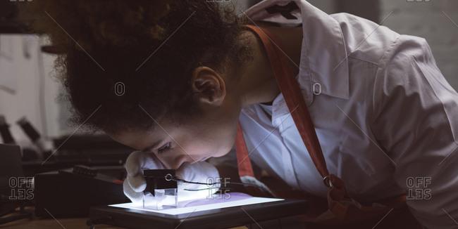 Female photographer using pocket magnifier in photo studio