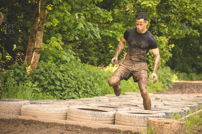 Fit man training over tires obstacle course at boot camp
