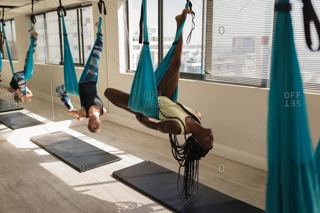 Group of women exercising on swing sling hammock at fitness studio