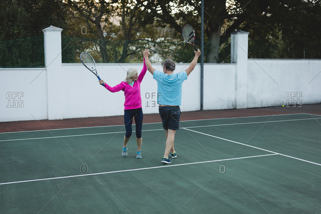 Happy senior couple cheering in tennis court
