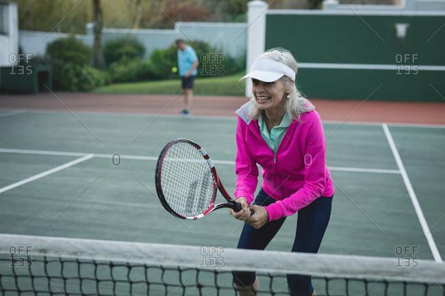 Happy senior woman playing tennis in tennis court