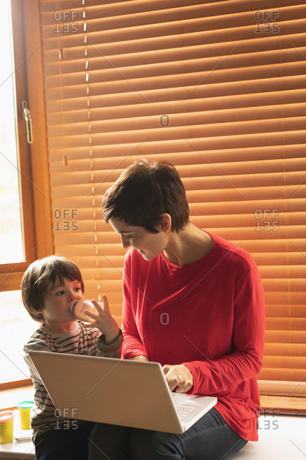 Mother and son sitting with a laptop at home